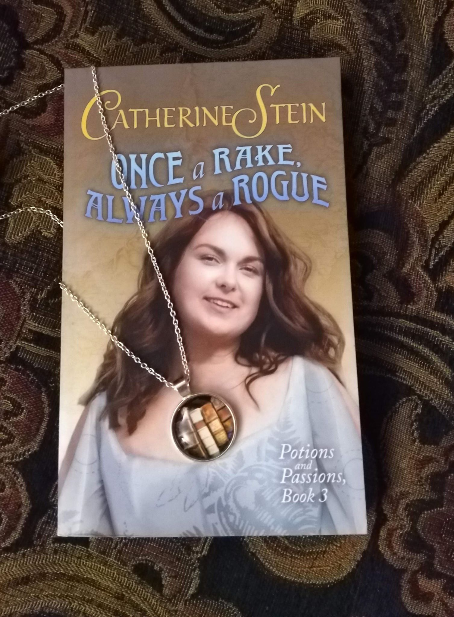 paperback copy and necklace with book pendant